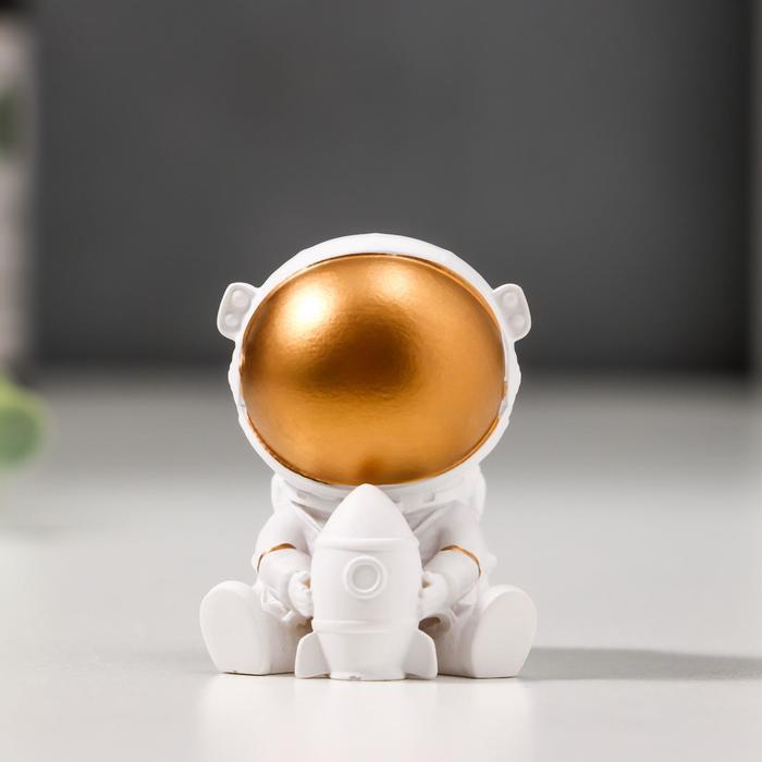 Сувенир полистоун Астронавт в белом скафандре с золотым шлемом, с ракетой 4х3,5х3 см